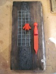 Plank amulet with red peg